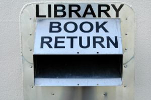 Metal library book drop slot on a wall