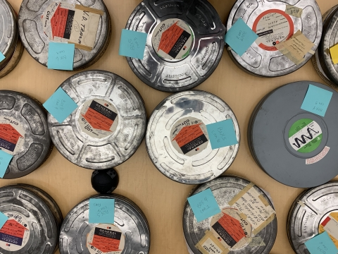 Film reels are laid out on a table and organized by title.